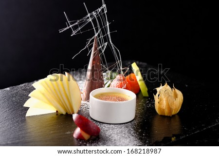 Haute cuisine, dessert Creme brulee and chocolate parfait with fruit - stock photo
