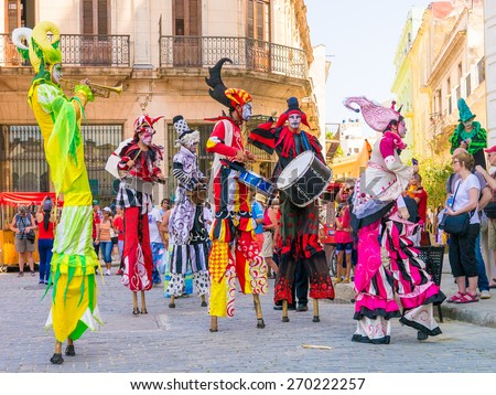 HAVANA, CUBA - APRIL 15,2015 : Colorful stiltwalkers dancing to the sound of cuban music in Old Havana - stock photo