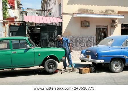 HAVANA, CUBA - APRIL 6, 2014: Cuban man making repairs to an old car on the street.  - stock photo