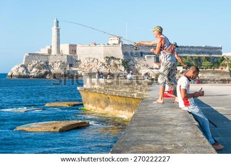 HAVANA, CUBA - APRIL 14,2015 : Cubans fishing in front of the famous El Morro castle, a worldwide known cuban landmark - stock photo