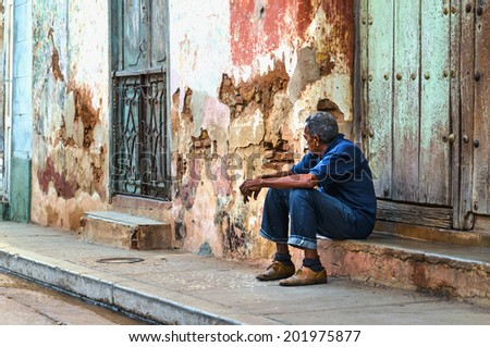 HAVANA, CUBA - DECEMBER 1, 2013: Cuban man resting in shadow on street of Trinidad, where temperature even in winters is often above 30 Celsius degrees. - stock photo