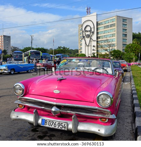 HAVANA, CUBA - JAN 20, 2016:  Tourists check out the vintage cars being used as taxis at Revolution Square.  The Ministry of Communications with Camille Cienfuegos can be seen in the background. - stock photo