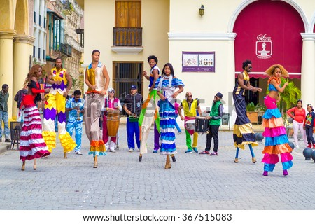 HAVANA,CUBA- JANUARY 24,2015 : Colorful band of street dancers on stilts and musicians on a beautiful Old Havana square - stock photo