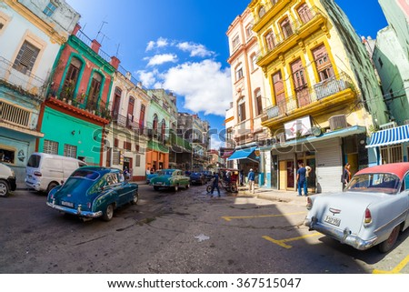 HAVANA,CUBA- JANUARY 19,2015 : Street scene with old classic cars and colorful buildings in Havana - stock photo