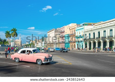 HAVANA, CUBA - JANUARY 8, 2015 : Street scene with people and traffic on a beautiful sunny day in Old Havana - stock photo