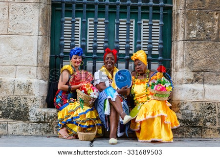 HAVANA, CUBA - JULY 17, 2013: Cuban ladies dressed in typical clothes posing for photos while smoking a huge cuban cigars in Havana, Cuba. - stock photo