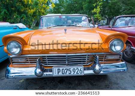 HAVANA,CUBA-JULY 12,2014: Old American cars for rent in central Havana. Due to scarcity,Cubans have kept old cars from 1950s running and nowadays is one important source of income - stock photo