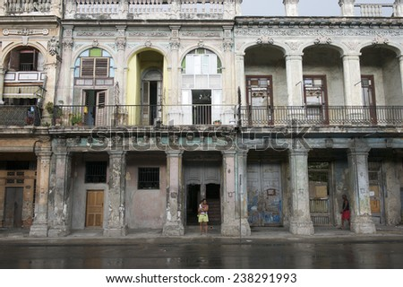 HAVANA, CUBA - JUNE, 2011: Cubans go about their daily lives against a background of classic colonial architecture on the facade of a crumbling building in central Havana. - stock photo