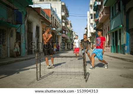HAVANA, CUBA - JUNE 23: Unidentified young men playing soccer in the streets of Havana. Havana, Cuba, June 23, 2013. Sport is very popular in Cuba, a lot of people practicing sports in the street. - stock photo
