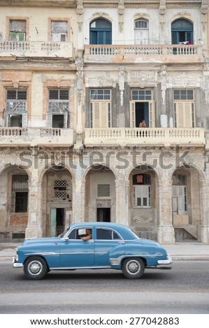 HAVANA, CUBA - JUNE, 2011: Vintage blue American car serving as taxi drives in front of classic colonial architecture on the Malecon in Central Havana. - stock photo
