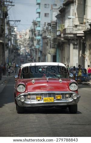 HAVANA, CUBA - JUNE 13, 2011: Vintage red American taxi drives along a narrow street in Centro, Havana Cuba. - stock photo