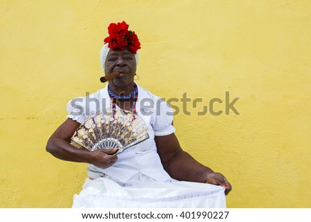 HAVANA, CUBA - MARCH 28, 2015: Cuban lady wears traditional clothing with cigar and fan while sitting on a chair in the old town of Havana, Cuba. - stock photo
