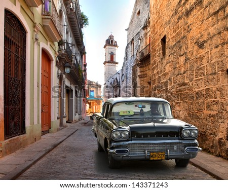 HAVANA, CUBA-MAY 14: Street scene with an old rusty american car on May 14, 2013 in Havana.These classic vintage cars that can be seen all over the country have become a worldwide known symbol of Cuba - stock photo