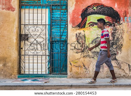 HAVANA,CUBA - MAY 20,2015 : Young cuban man walks by a colorful Che Guevara portrait painted on a shabby  old wall in Old Havana - stock photo