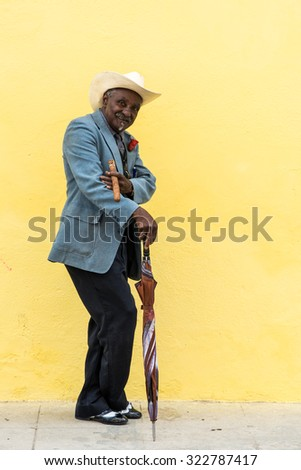 Havana, Cuba - September 27, 2015: Traditional Cuban man posing for photos while smoking big cuban cigar on yellow wall background in Havana, Cuba. - stock photo