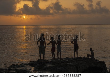 HAVANA/CUBA 4TH JULY 2006 - Kids playing on the Malecon at Sunset - stock photo