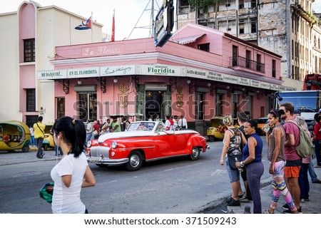 HAVANA - January 5, 2016: El Floridita restaurant and bar in Havana, Cuba The Floridita is an famous historic bar in Havana, known for Hemingway and daiquiris. old cars, people walking in the street - stock photo