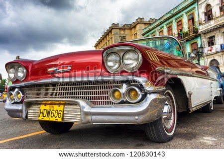 HAVANA-NOVEMBER 28:Old red Chevrolet near the Capitol November 28,2012 in Havana.Thousands of these cars are still in use in Cuba and they have become an iconic view and a worldwide known attraction - stock photo
