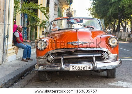 HAVANA-SEPTEMBER 10:Vintage red Chevrolet parked near El Prado street September 10,2013 in Havana.These old classic cars have become an iconic sight and a tourist attraction in the Cuban cities - stock photo