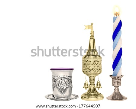 Havdalah set.Silver kiddush wine cup,gold color spice box,braided lit candle.Jewish religious ritual after end of Sabbath.Spice container,traditional tower shape,bell and flag.Horizontal photo. - stock photo