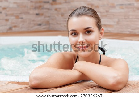 Have a splendid time. Close-up of a young beautiful woman enjoying a jacuzzi in a spa center - stock photo