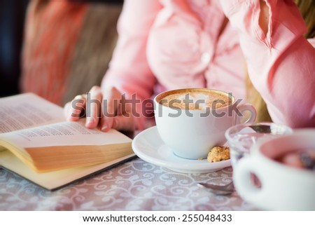 Have break / Close up photo from a cappuccino with a woman reading a book - stock photo