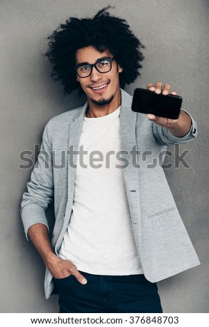 Have you seen my new smart phone?Cheerful young African man showing his smart phone and smiling while standing against grey background - stock photo