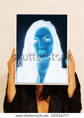 Having a negative head.  Surreal picture of woman holding a picture frame which gives a negative image of her head within the frame - stock photo