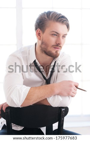Having a smoking break. Thoughtful young man in shirt and tie smoking a cigarette and looking away while sitting on the chair - stock photo