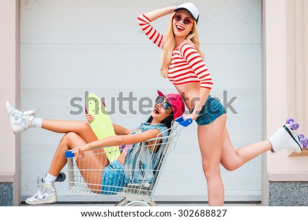 Having crazy day together. Side view of happy young woman on roller skates carrying her female friend in shopping cart and smiling while skating against the garage door - stock photo