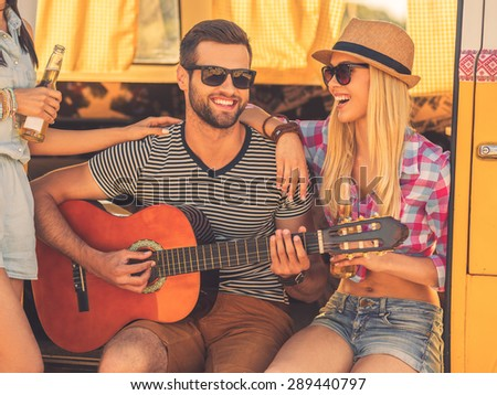 Having fun after long road trip. Handsome young man sitting in minivan and playing guitar while two young women bonding to him   - stock photo