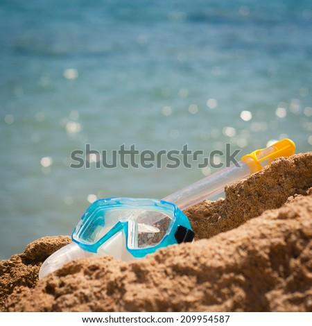 Having fun at the sea: closeup of a diving mask and snorkel lying on a rock at the seashore - stock photo