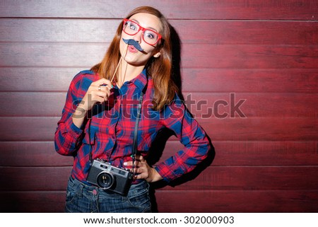 Having fun. Attractive young woman holding paper mustache on her face. - stock photo