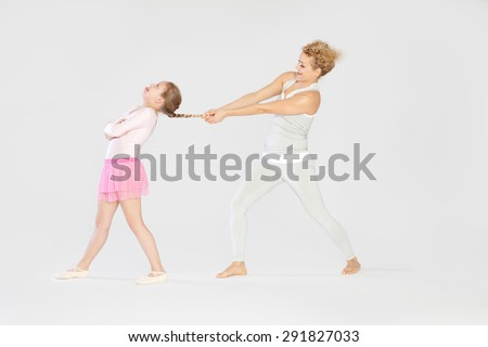 Having fun / Mother pulling her daughters fishtail braid - stock photo