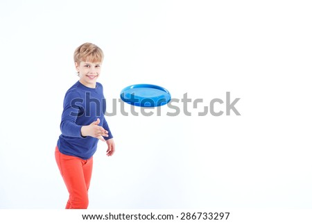 Having fun. Pleasant boy smiling and playing Frisbee while standing isolated on white background. - stock photo