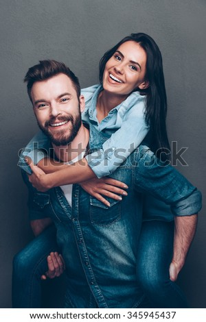 Having fun together. Handsome young man piggybacking beautiful woman and smiling while standing against grey background - stock photo