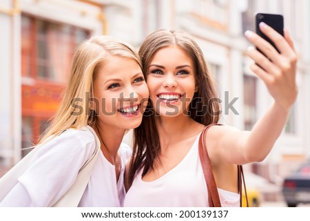 Having fun together. Two beautiful young women making selfie and smiling while standing outdoors - stock photo