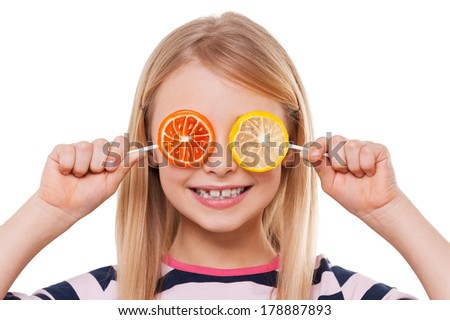 Having fun with candies. Cheerful little girl covering eyes with lollipops and smiling while isolated on white - stock photo