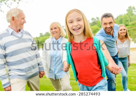 Having fun with family. Happy little girl enjoying time with her family while walking outdoors together  - stock photo