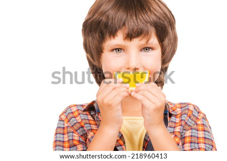 Having fun with orange. Cheerful little boy covering mouth with piece of orange while isolated on white - stock photo