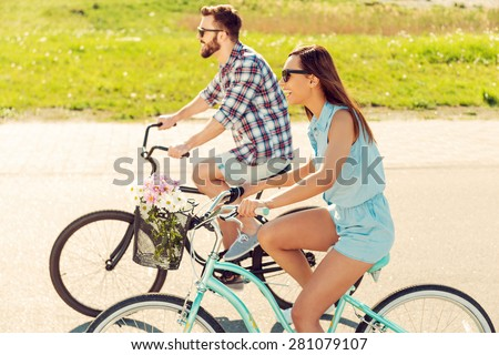Having great time together. Cheerful young couple riding bicycles together and smiling - stock photo