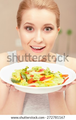 Having lunch. Young woman looking surprised and happy holding and giving you a plate with fresh salad - stock photo