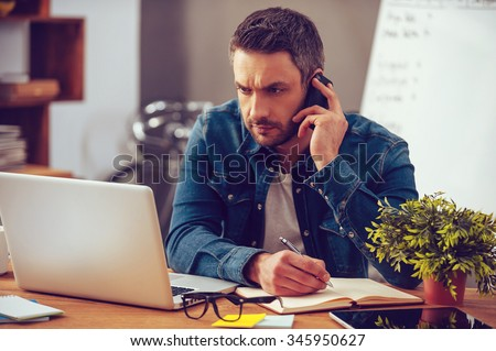 Having so much work to do. Confident young man working on laptop and talking on the mobile phone while sitting at his working place in office - stock photo