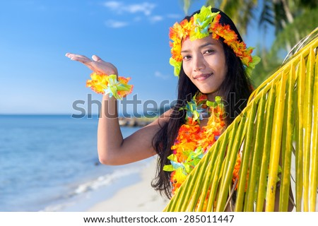 Hawaii hula dancers on the tropical sea beach invitation to an exotic tropical vacation  with a palm leaf shows blue sky.  - stock photo
