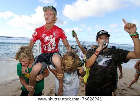 HAWAII - JANUARY 27: John Florence is carried up the beach by his friends after winning the final of the Volcom Pipeline Pro Jan. 27, 2011 on the North Shore of Hawaii. - stock photo