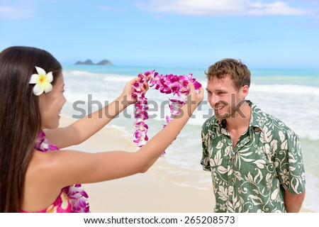 Hawaii woman giving lei garland of pink orchids welcoming tourist on Hawaiian beach. Portrait of a Polynesian culture tradition of giving a flower necklace to a guest as a welcome gesture. - stock photo