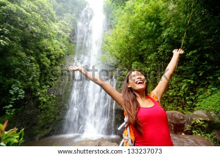 Hawaii woman tourist excited by waterfall during travel on the famous road to Hana on Maui, Hawaii. Ecotourism concept image with happy backpacking girl. Mixed race Asian / Caucasian backpacker. - stock photo