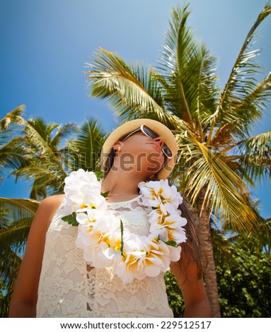 Hawaii woman with flower lei garland of white flowers. Portrait of a beautiful young woman in white dress. Welcoming Lei on the hawaiian island Honolulu. - stock photo