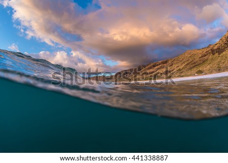 Hawaiian abstract ocean scenery as travel design template with underwater part and sunset skylight splitted by waterline. Beautiful clouds and bright sun over sea water. - stock photo