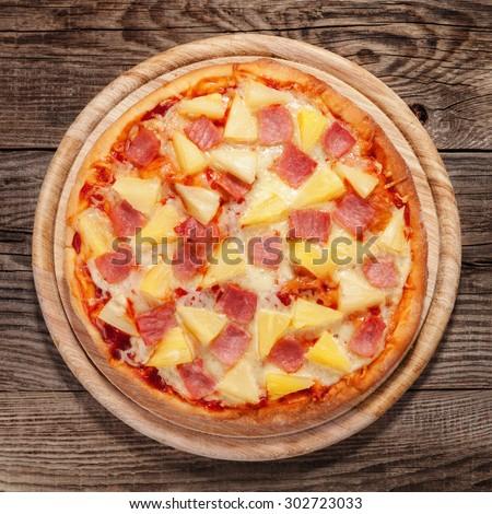 Hawaiian pizza on the old table. - stock photo